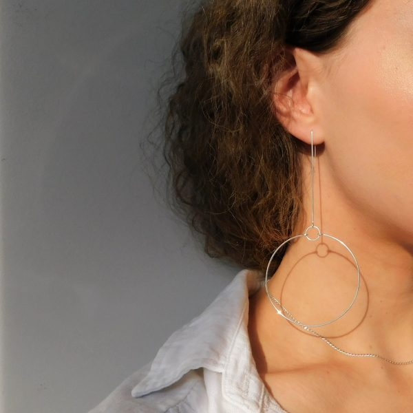 Long silver terrestrial earrings on model