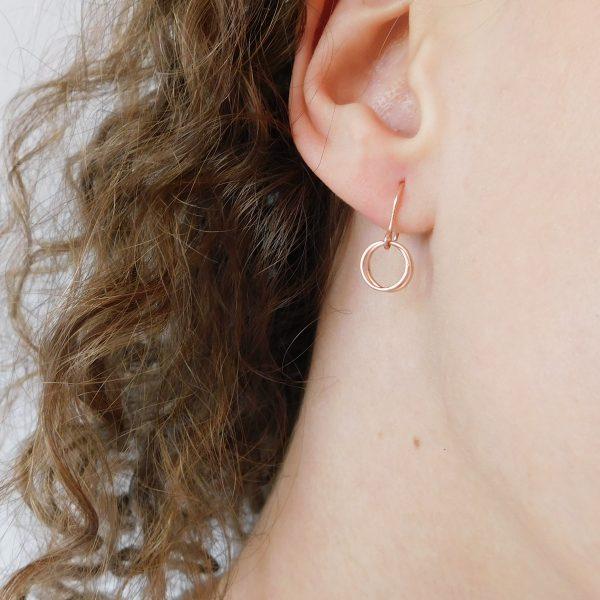 rose gold serenade earrings on model