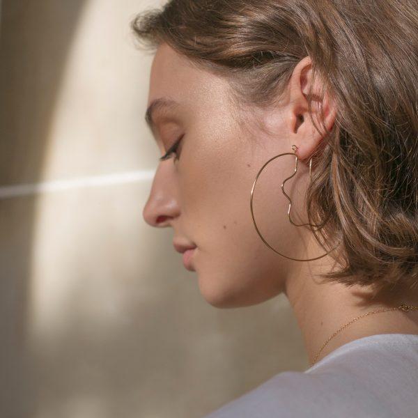 Model wearing gold lagoon hoop earrings