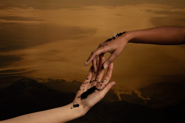 two hands touching with the dynasty ring balanced on one hand and the other hand wearing the ring