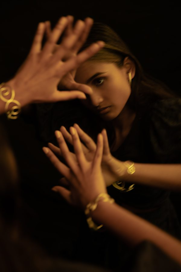 model wears prevail bangle while looking at herself in the mirror and placing her hands on the mirror