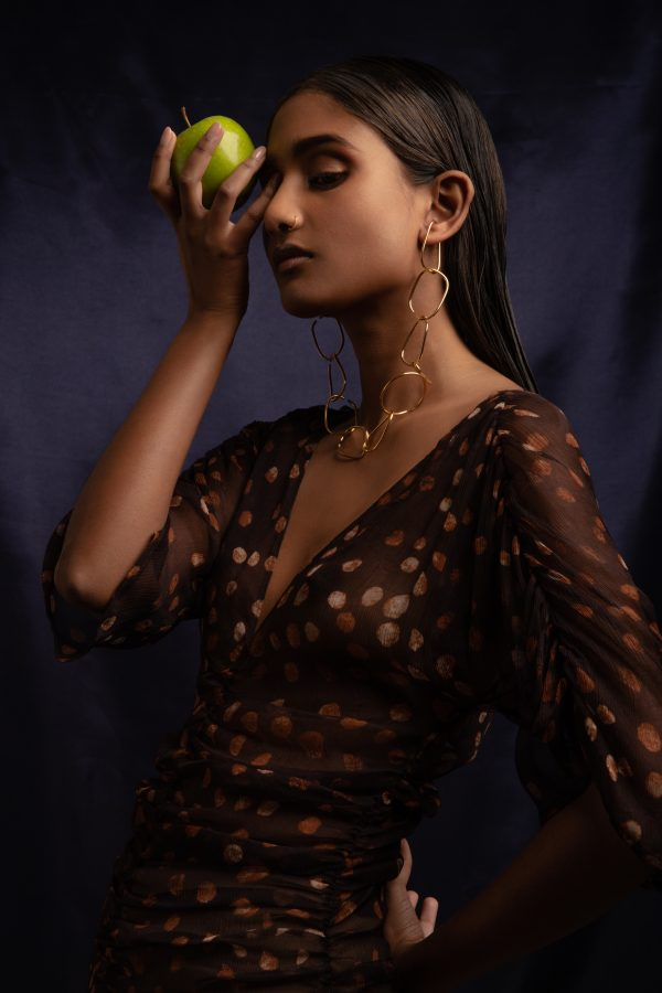 model wears eternal ear cuff made into a chain while holding an apple up to her face