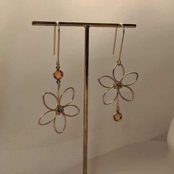 Gold flora earrings with yellow gem hanging on stand