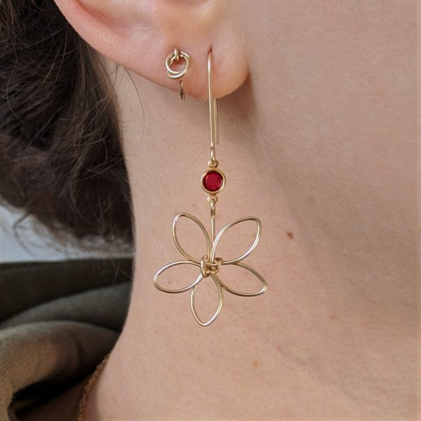 Gold flora earrings with red gem on ear
