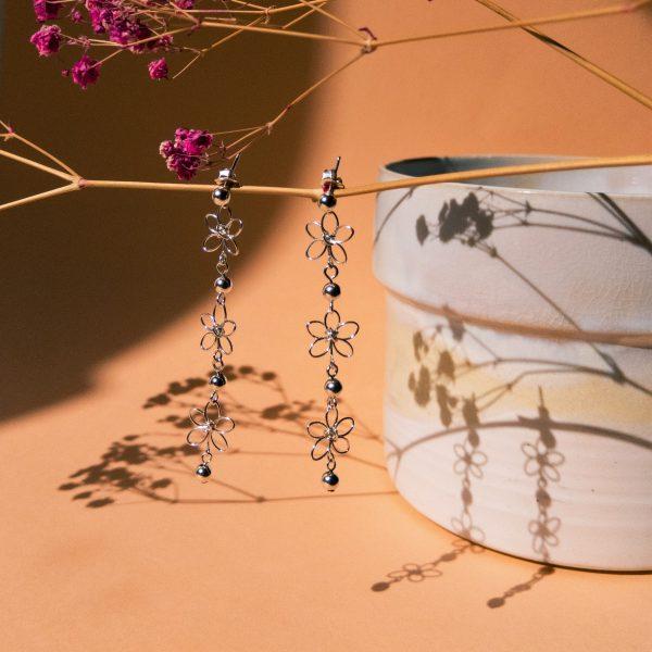 carnation earrings hanging from flower stem