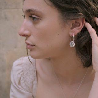 Tide pool hoop earrings on model