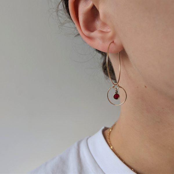 model wearing gold gem hoop earrings with siam january july birthstone