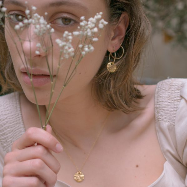 Model wearing gold stream hoops holding flower in front of face