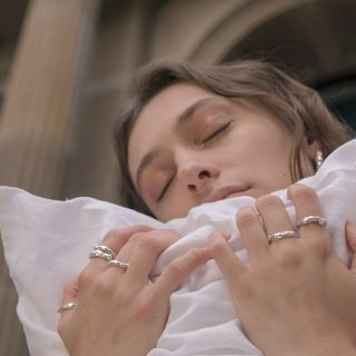 Model wearing molten rings holding pillow