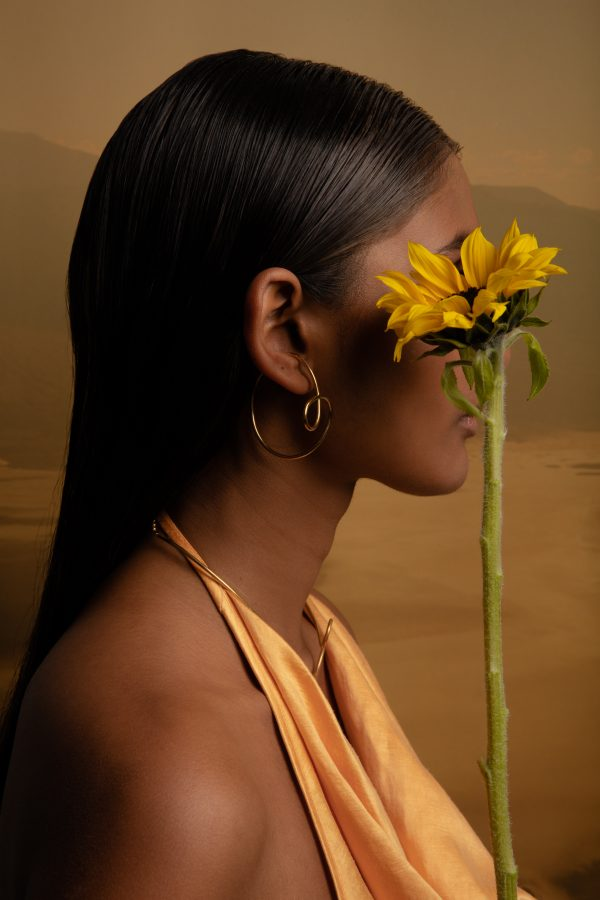 model wears dynasty ear cuff while holding a flower in front of her face