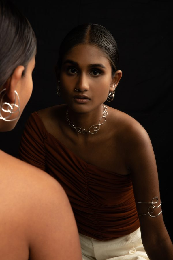 Model wearing divinity ear cuffs, prevail choker and dynasty bangles while looking at herself in the mirror
