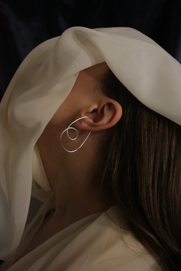 divinity ear cuff on model with chiffon fabric covering face