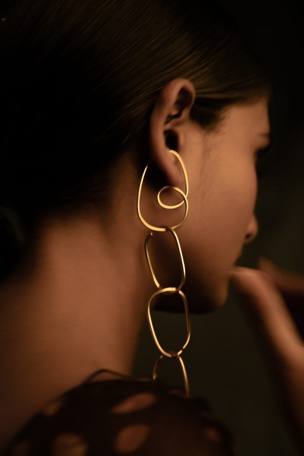 model wearing divinity ear cuff with chain of eternal ear cuffs hanging off