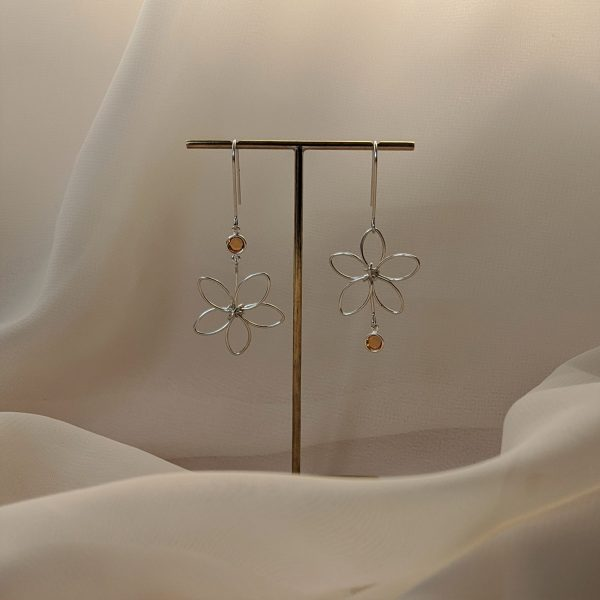 Silver flora earrings with yellow gem hanging on stand