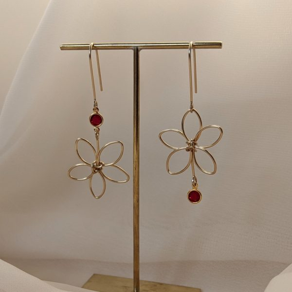 Gold flora earrings with red gem hanging on stand