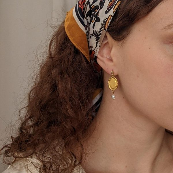 gold portrait earrings on ears