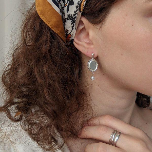 silver portrait earrings on ears