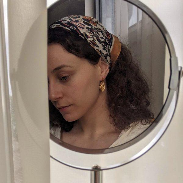 gold flourish earrings on ear