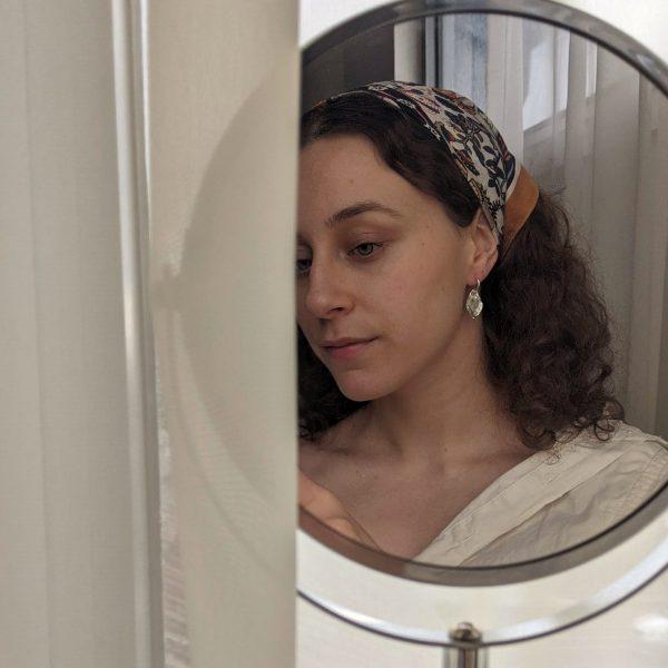 silver flourish earrings on ear