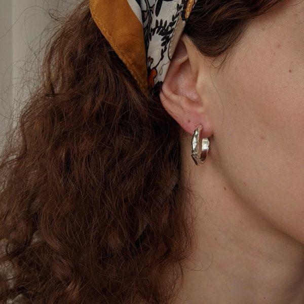 silver reminiscent earrings on ear