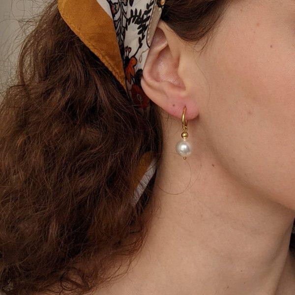 gold ornate earrings on ears