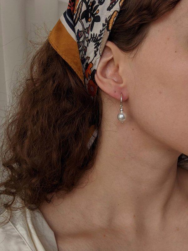 silver ornate earrings on ears