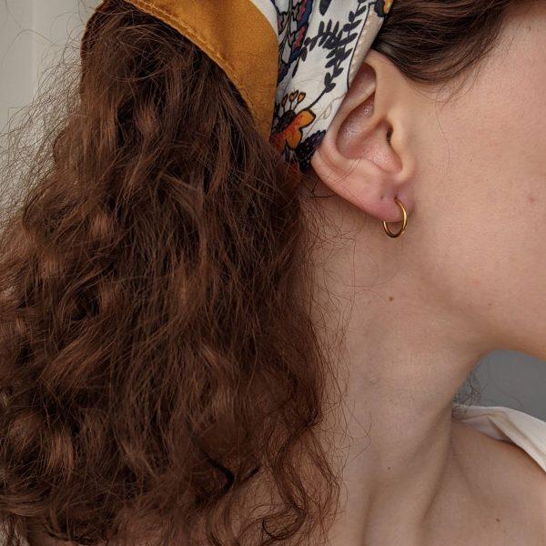 gold repertoire earrings on ear