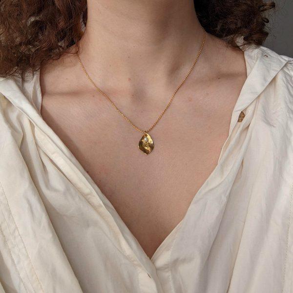 gold flourish necklace on neck