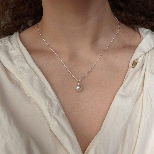 silver ornate necklace on neck