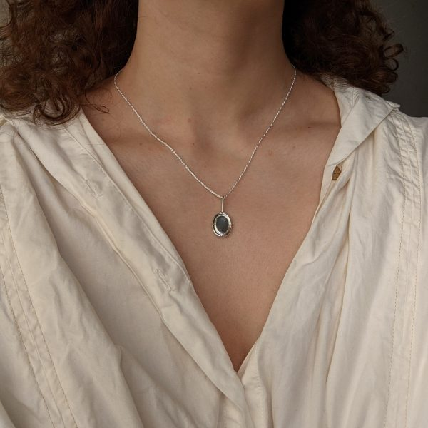 silver portrait necklace on neck