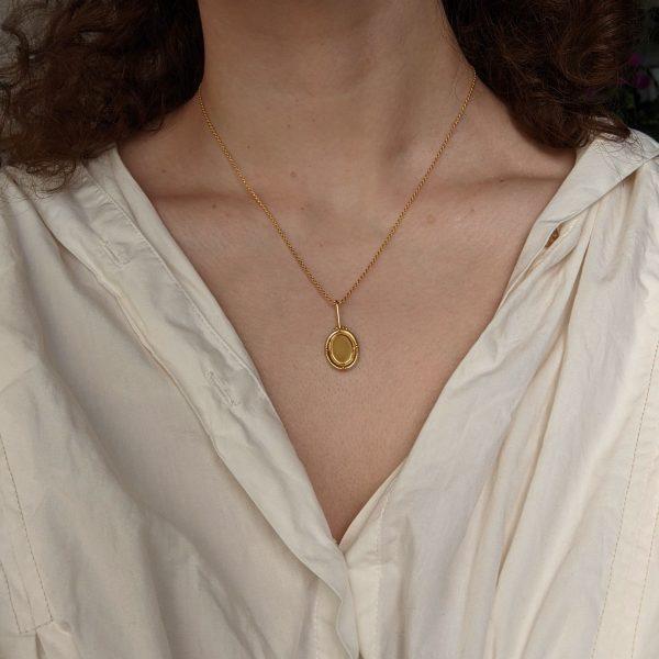 gold portrait necklace on neck